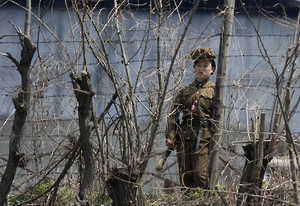 A North Korean prison policewoman stands guard behind fences at a jail on the banks of Yalu River near the Chongsong county of North Korea, opposite the Chinese border city of Dandong on May 8, 2011. © 2011 Reuters