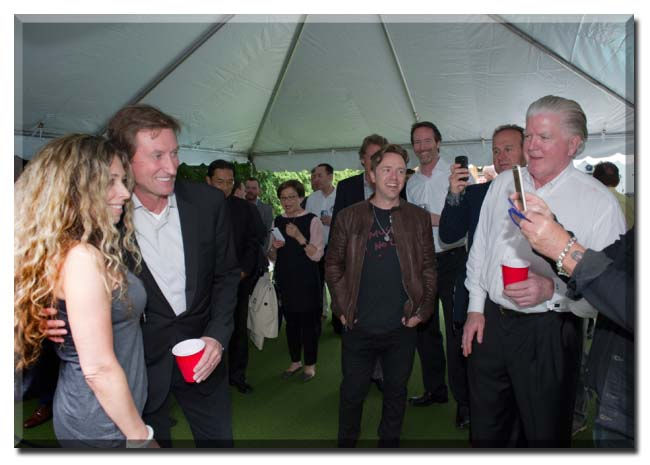Hockey great Wayne Gretzky has his picture taken with a fan as president of Hockey Operations for the Calgary Flames Brian Burke looks on during The 2nd Annual Night for Change in Toronto on June 8, 2015. Kevin Van Paassen for National Post.
